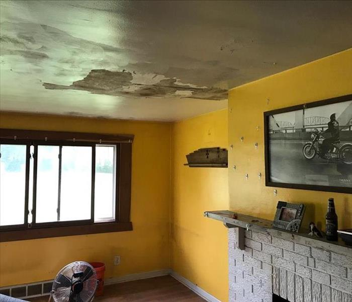 yellow living room with damaged ceiling, pieces of drywall exposed