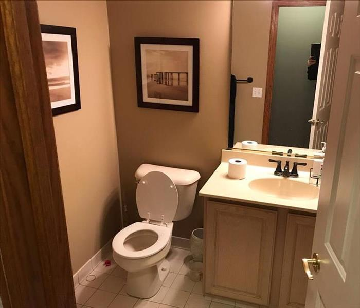 bathroom with tile floor, white toilets, clear plastic bucket of water to right of toilet