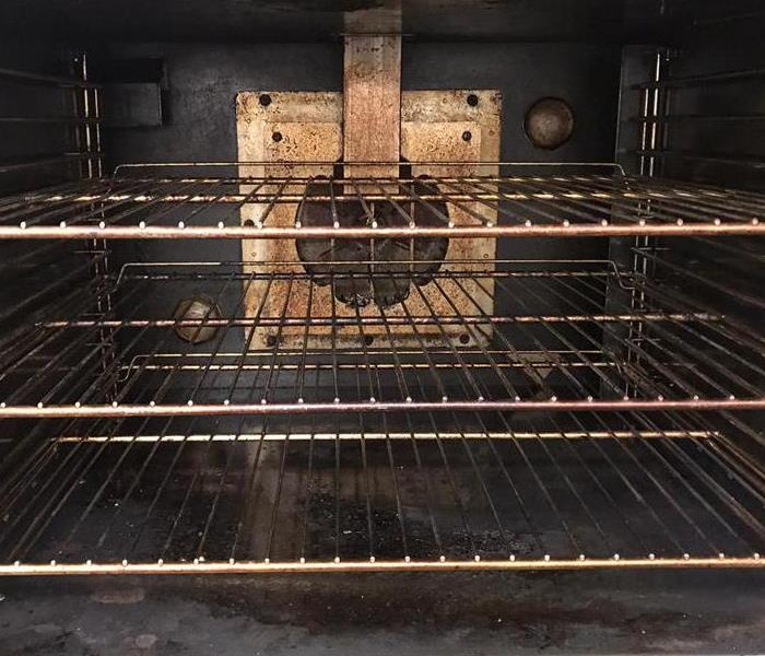 inside of oven with dirt on the racks, walls, and lower shelf