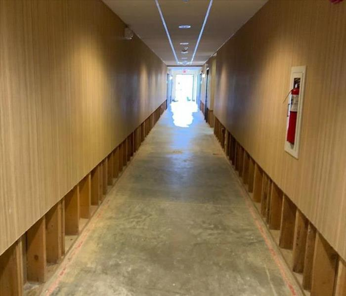 long hallways with concrete ground and exposed floor baseboards
