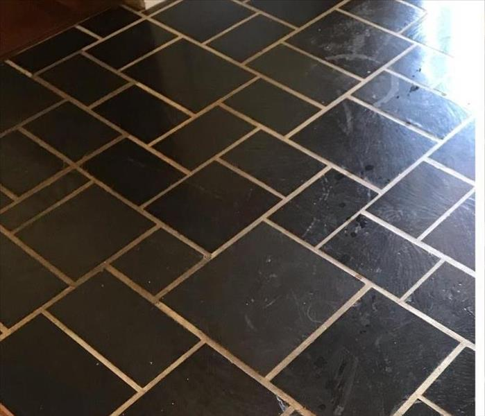 black and white tile floor with dirt and scuff marks, dull appearance