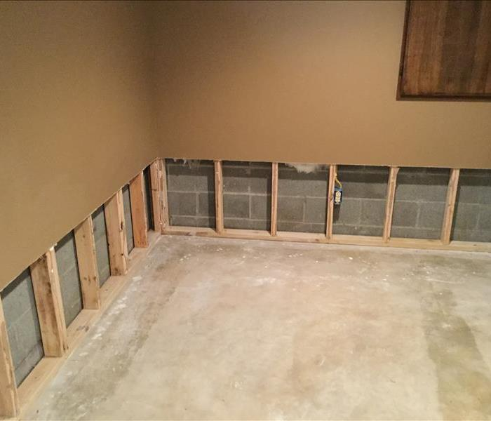 concrete basement with cuts in the drywall