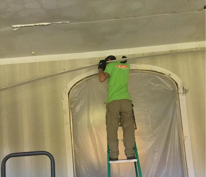 servpro employee on ladder holding crown molding