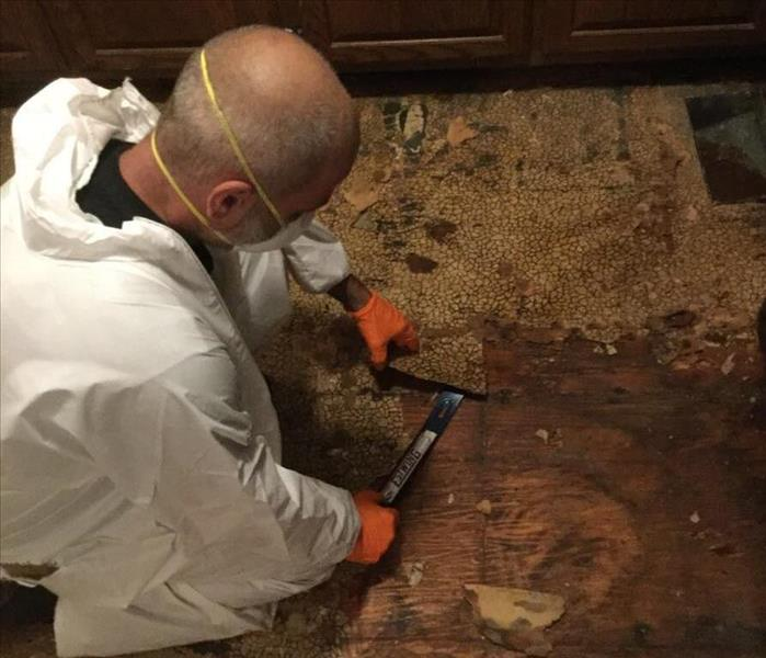 servpro employee wearing gloves and tearing out the tile floor in a kitchen