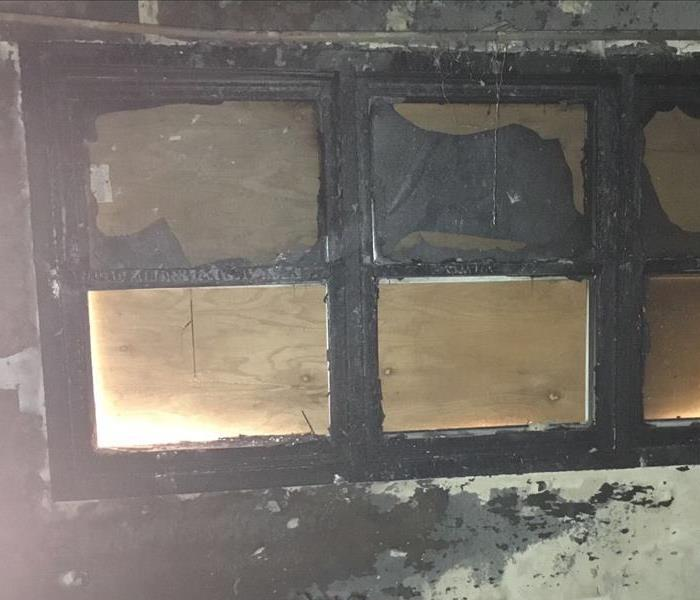 six windows with heavy soot damage and a wooden board on the outside