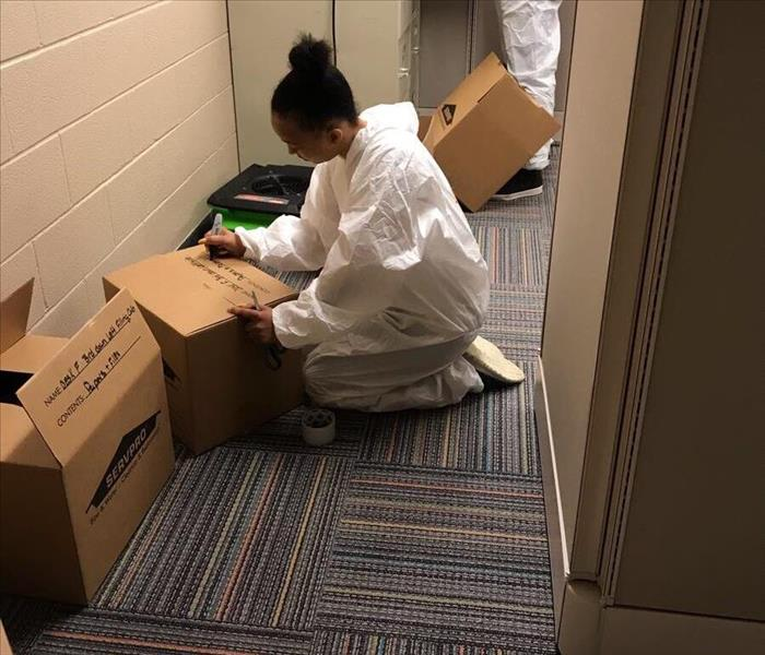 servpro employees in PPE gear organizing contents in a carpeted office and placing belonging into servpro boxes
