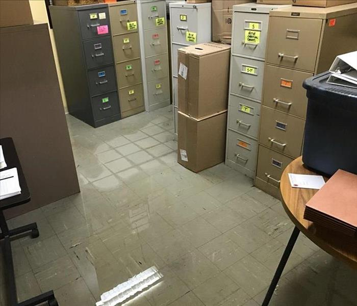 several feet of water in an office storage room with standing file cabinets