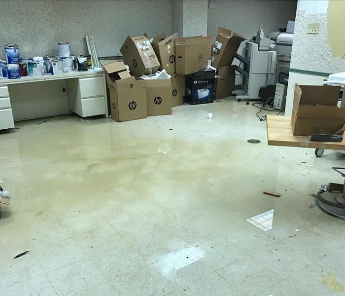 puddles of floor in the middle of the warehouse with contents and debris spread throughout