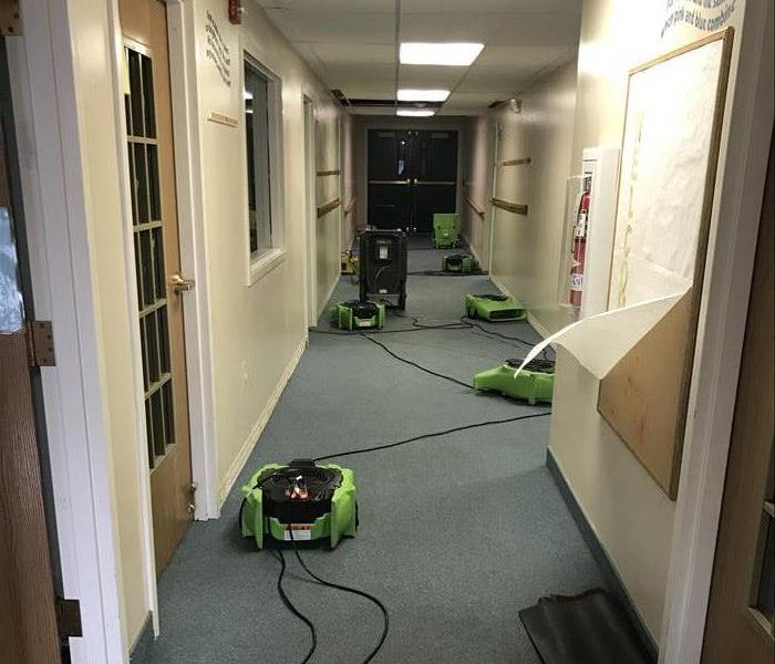 narrow hallway with blue carpeting and air movers and dehumidifiers spread throughout