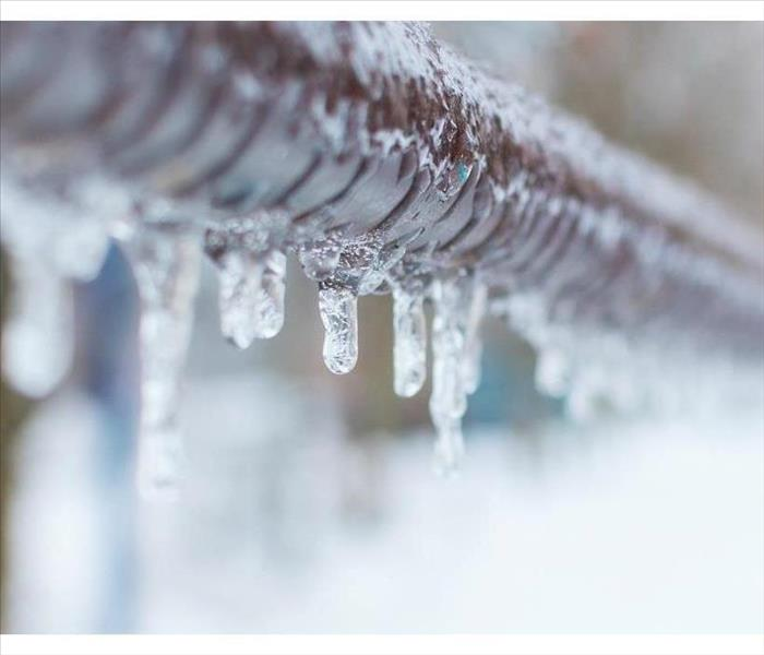 image of frozen water droplets hanging from a metal pipe