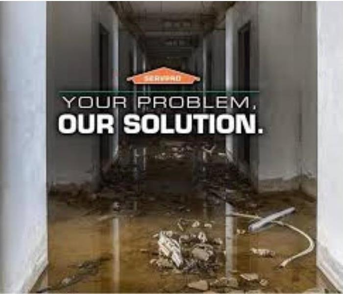 "soiled hallway in background with text on top, ""Your problem, our solution"" under the SERVPRO logo"