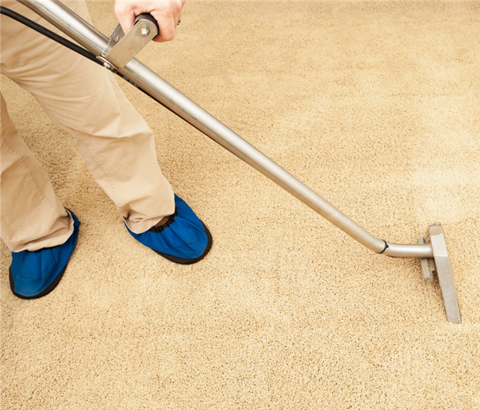 Picture shows a man holding a carpet cleaner extracting water from carpet