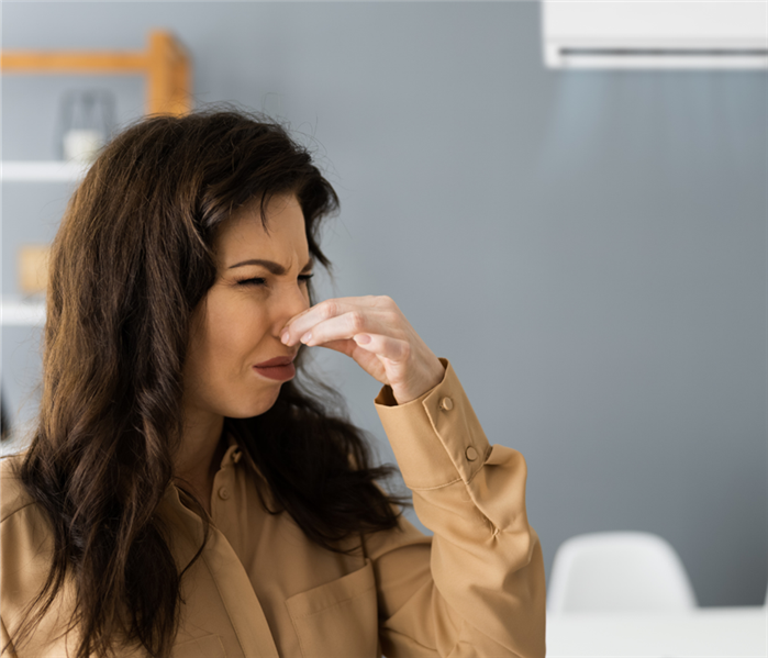 Woman pinching nose and wincing due to a smell.