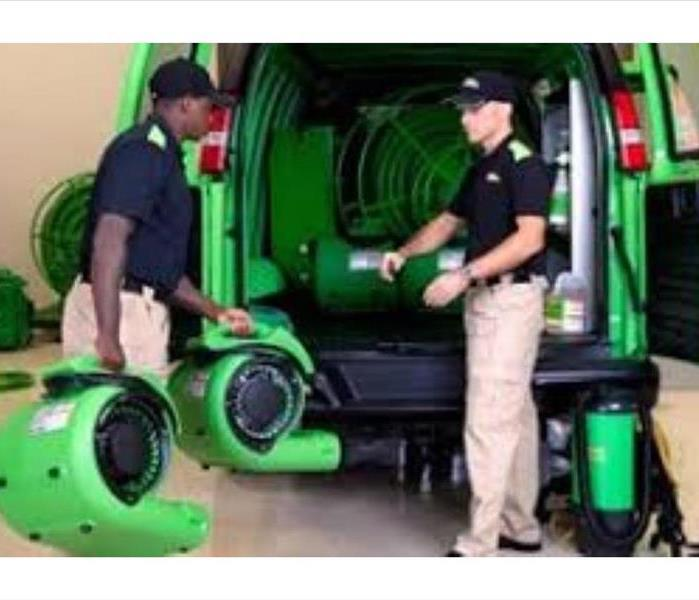 uniformed servpro employees unloading dehums off the back of servpro van