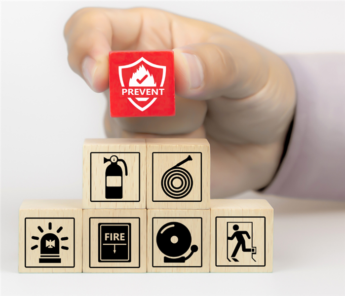 Picture shows a hand stacking up small wooden blocks that have cons that cause fire. The top blocks says prevention.