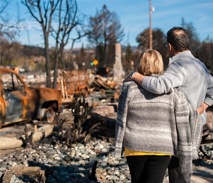 Picture shows a couple standing next to their burnt down house
