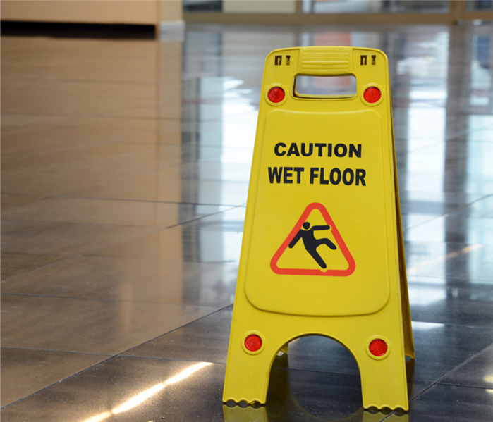 "A yellow sign saying ""Slippery When Wet"" sits on the floor."