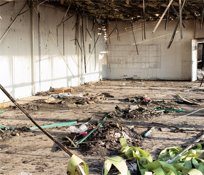 Picture shows a large commercial space completely affected by fire. The roof is wood beams and there is ash everywhere.